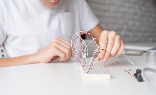 Mãos de menino trabalhando com luzes led em uma placa experimental para projeto de ciências
