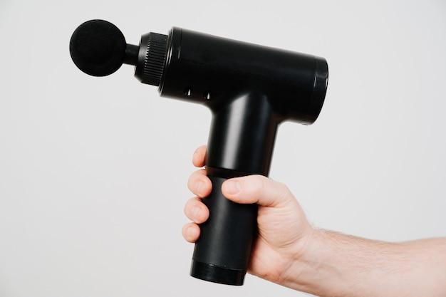 Mãos de mens detém pistola de massagem. dispositivo de esportes médicos ajuda a reduzir a dor muscular após o treino