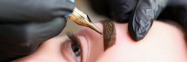 Mãos de mestres de beleza fazem maquiagem permanente sobrancelha. trauma mínimo na pele. a microblading das sobrancelhas é realizada usando a alça do manipulador e um bico especial com agulhas. nível de habilidade cosmetologist