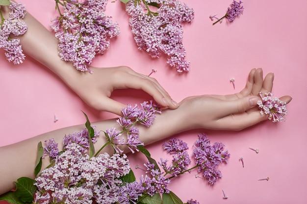 Mãos de modelo de moda com flores lilás roxas brilhantes