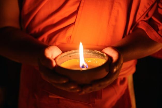 Mãos de monge budista segurando a taça de vela no escuro, chiang mai, tailândia
