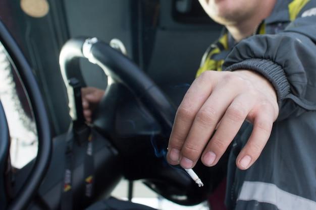 Mãos de motorista de caminhão ou ônibus segurando o volante e fumando cigarro em locais públicos.