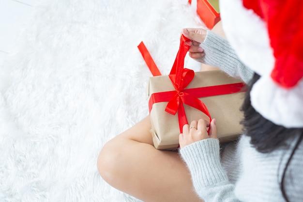 Mãos de mulher abrindo presente de natal