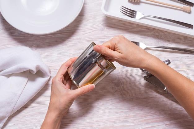 Mãos de mulher, abrir a lata com carne em lata, mesa da cozinha vista superior