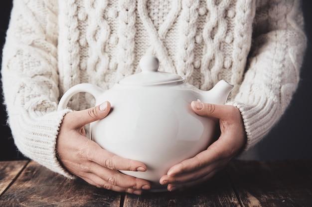Mãos de mulher adulta abraçam grande bule de cerâmica com bebida quente dentro.