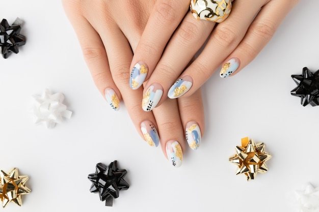 Mãos de mulher adulta jovem com unhas elegantes em fundo branco. desenho de unhas primavera verão. manicure, pedicure conceito de salão de beleza.