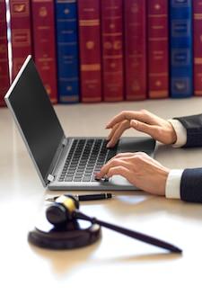 Mãos de mulher advogada com martelo judicial durante consulta online com o cliente. escritório de advogados.