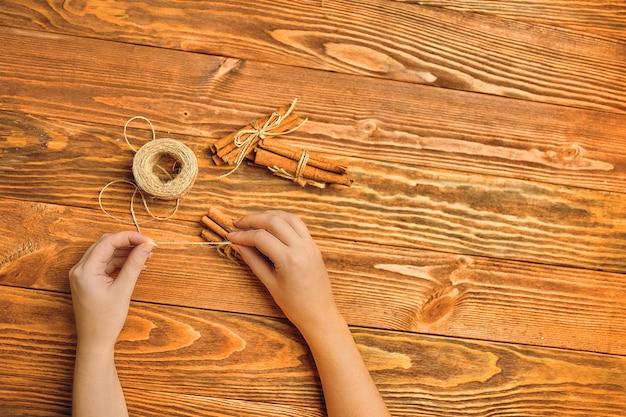 Mãos de mulher amarradas com canela tubo de corda sobre a mesa de madeira