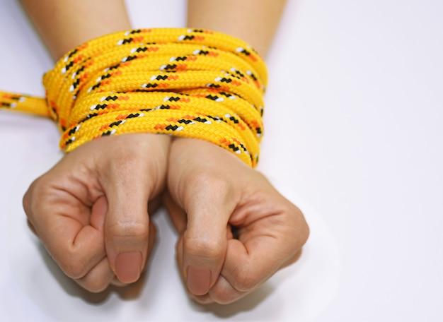 Mãos de mulher amarradas com corda.