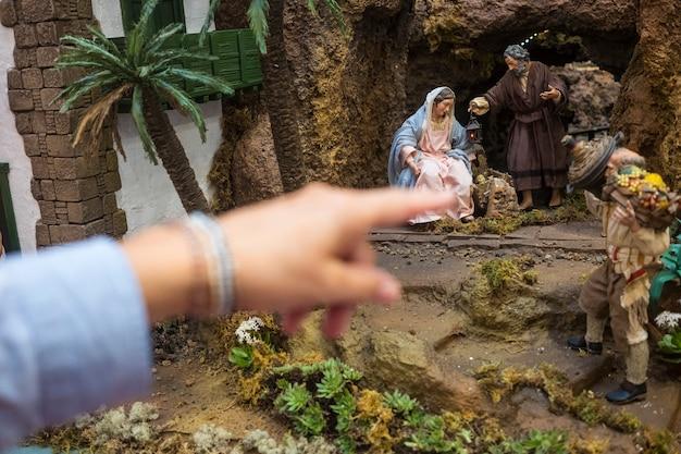 Mãos de mulher apontadas para o presépio de natal no shopping