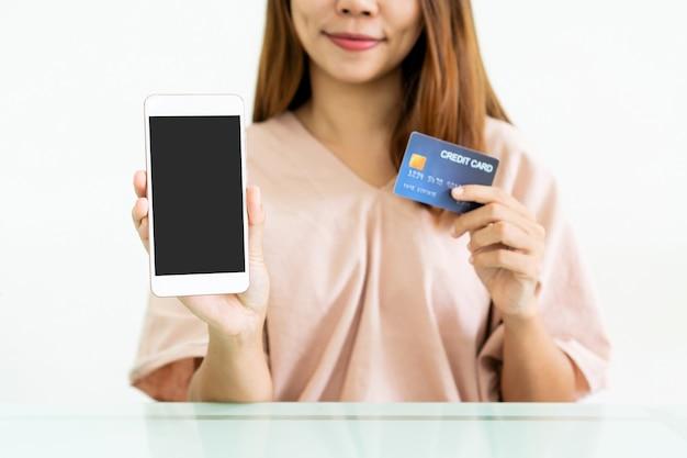 Mãos de mulher asiática mostram celular com tela em branco para espaço de cópia, propaganda enquanto segura o cartão de crédito