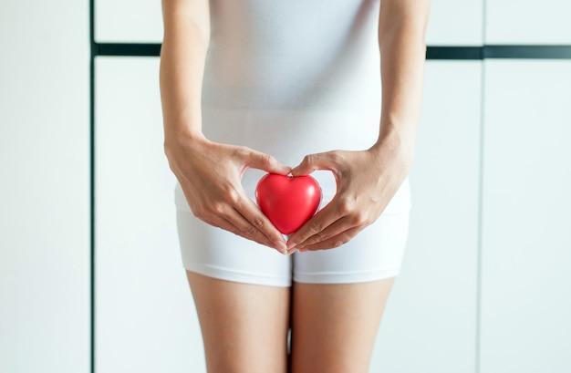 Mãos de mulher asiática segurando modelo coração vermelho na virilha com leucorréia