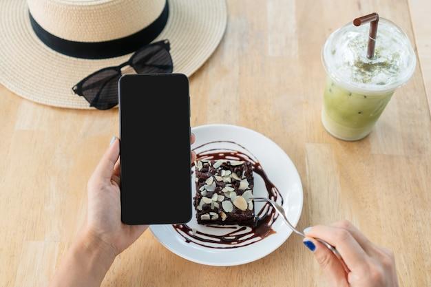 Mãos de mulher asiática usando smartphone enquanto come bolo de brownie com leite matcha gelado