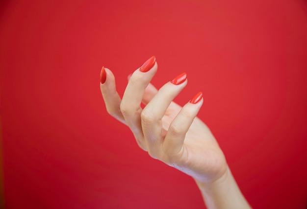 Mãos de mulher bem cuidada sobre fundo vermelho.
