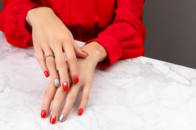 Mãos de mulher bem cuidadas com desenho de unhas de natal em fundo cinza mármore