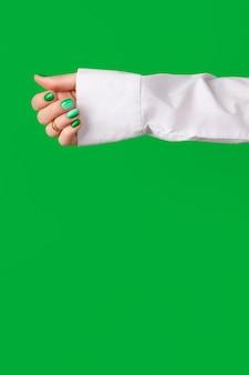 Mãos de mulher bem cuidadas com design de unhas verdes na superfície verde
