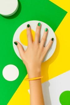 Mãos de mulher bem cuidadas com superfície geométrica de unhas verdes