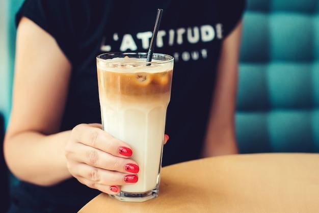 Mãos de mulher bonita com café com leite frio no café moderno. pausa para o café. café com leite com gelo. clima de café no verão.