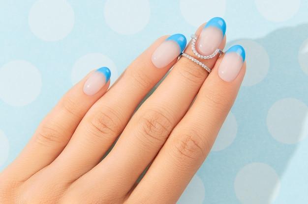 Mãos de mulher bonita com design de unhas na moda no fundo azul