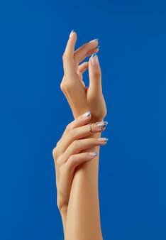 Mãos de mulher bonita com design de unhas na moda sobre fundo azul