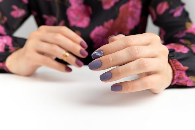 Mãos de mulher bonita com manicure roxo cor de vinho fosco.
