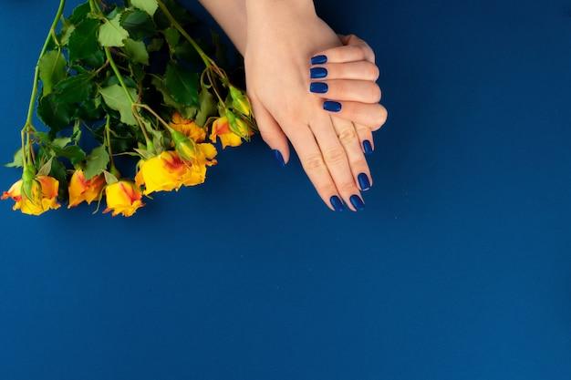 Mãos de mulher bonita com manicure segurando rosas