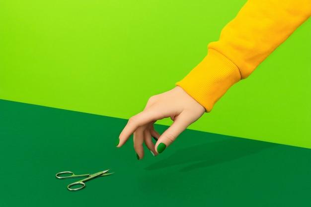 Mãos de mulher bonita e bem cuidada com unhas verdes escolhendo uma tesoura na superfície verde