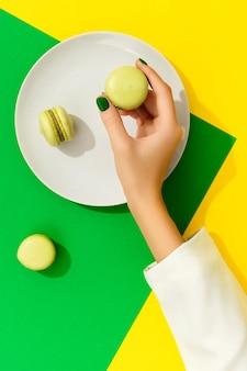 Mãos de mulher bonita e bem cuidada com unhas verdes segurando macarons na superfície verde e amarela