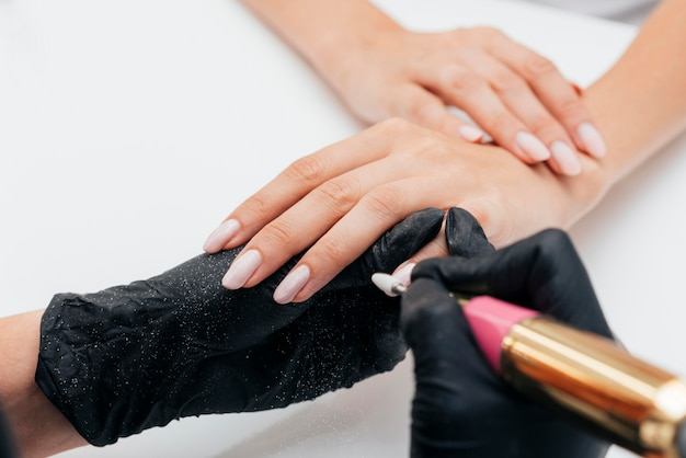 Mãos de mulher bonita e lixa de unha