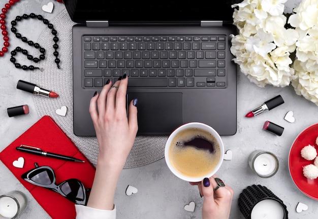 Mãos de mulher bonita preparada digitando no teclado na mesa do escritório em casa