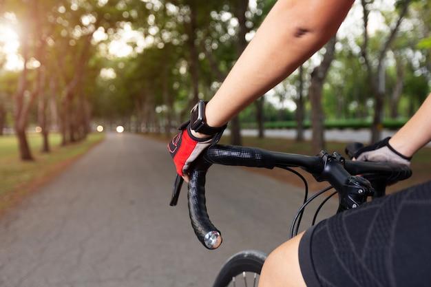 Mãos de mulher ciclista com ícone de frequência cardíaca no relógio inteligente, bicicleta na trilha de verão.