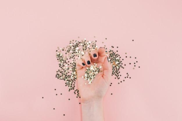 Mãos de mulher cobertas de confetes de estrelas douradas em rosa
