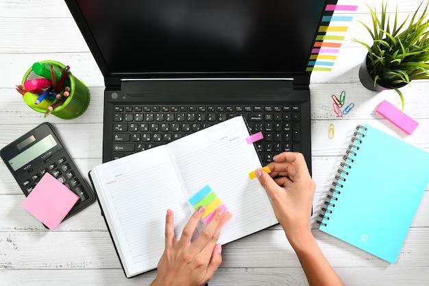Mãos de mulher colam adesivos coloridos no diário