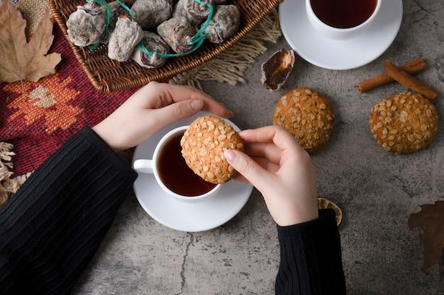 Mãos de mulher colocando biscoito de aveia em uma xícara de chá quente.