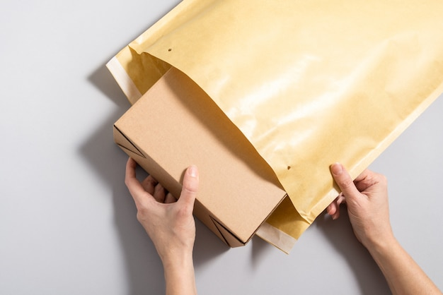 Mãos de mulher colocando caixa de papelão dentro de envelope postal grande