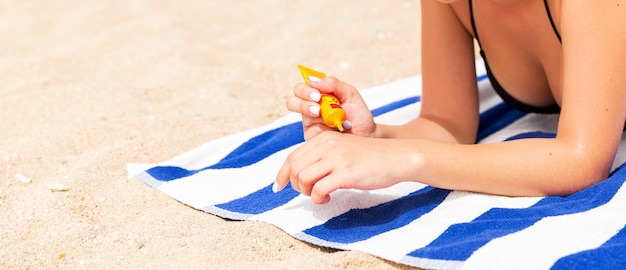Mãos de mulher colocando protetor solar de uma garrafa de suncream
