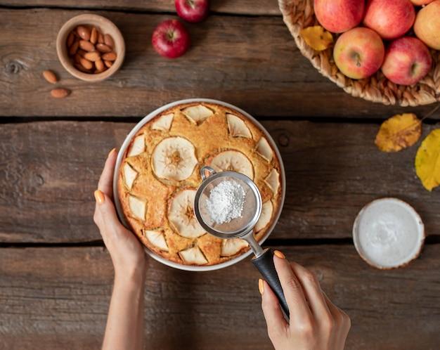 Mãos de mulher com açúcar de confeiteiro polvilhado na torta de frutas em um rústico de madeira