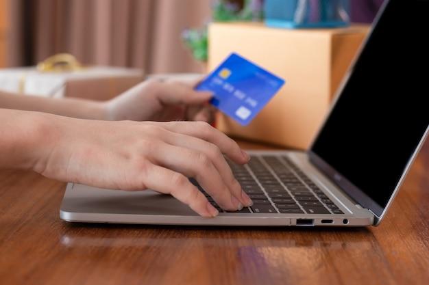 Mãos de mulher com alta tecnologia mantenha cartão de crédito usando o laptop para fazer compras online