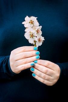 Mãos de mulher com as unhas pintadas de azul claro com um suéter azul escuro, segurando delicadamente um galho de flor de cerejeira