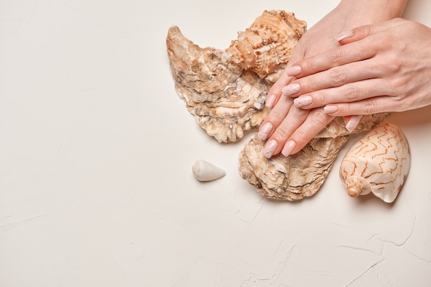 Mãos de mulher com bela manicure em fundo claro