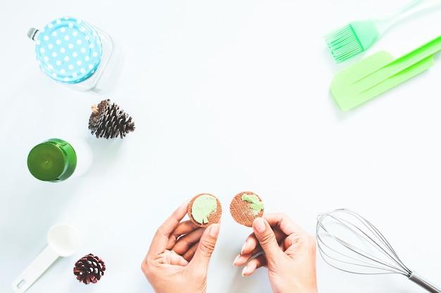 Mãos de mulher com biscoito de creme de chá verde macha e ferramentas de padaria na mesa branca, flat lay