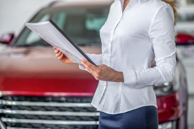 Mãos de mulher com blusa branca segurando um documento