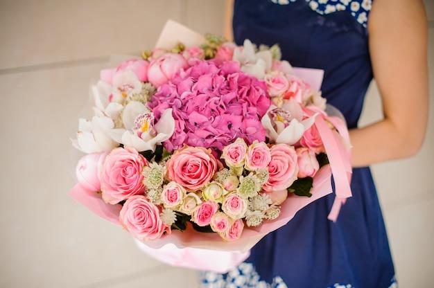 Mãos de mulher com buquê rosa bonito e suave