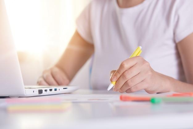 Mãos de mulher com caneta amarela escrevendo algo no peper, trabalhando on-line, feminino trabalhando no laptop
