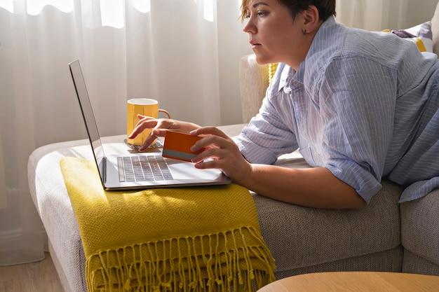 Mãos de mulher com cartão de crédito e usando laptop, fazendo compras online. aconchegante casa interior em cores claras durante a liquidação de outono. conceito de black friday e cyber monday