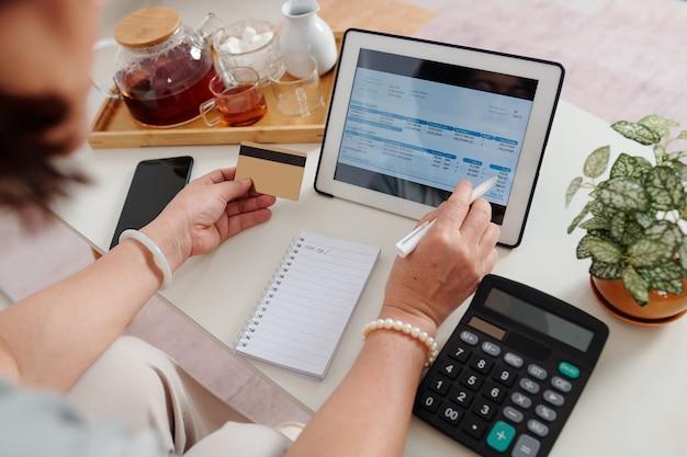 Mãos de mulher com cartão de crédito usando aplicativo no computador tablet ao pagar contas de serviços públicos