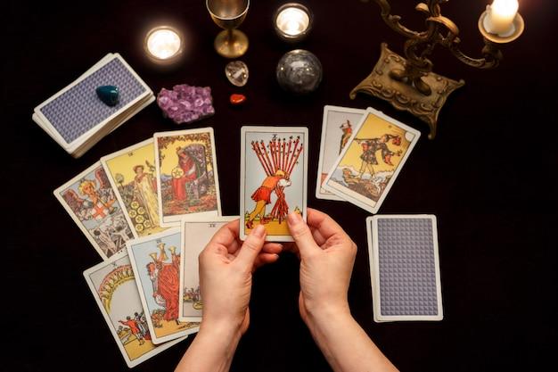 Mãos de mulher com cartas de tarô