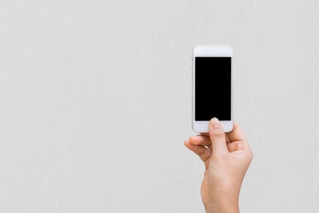Mãos de mulher com celular de parede, mock up