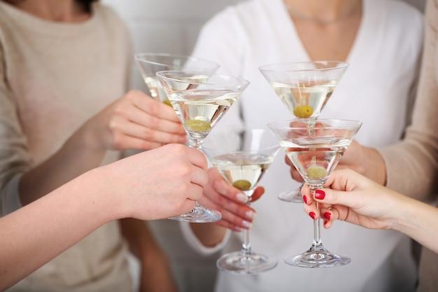 Mãos de mulher com copos de close-up de martini