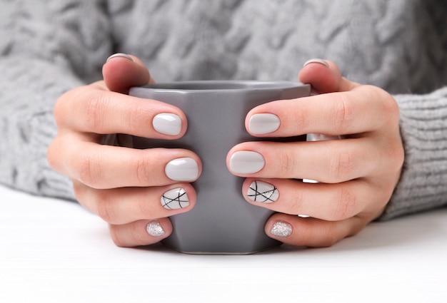 Mãos de mulher com design de unhas manicure geométrica na camisola acolhedora